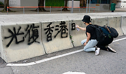 Protestor spraying graffiti onto barrier in Hong kong during pro-democracy demonstration