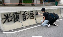Protestor spraying graffiti onto barrier in Hong kong during pro-democracy demonstration