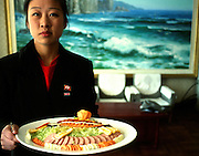 Dinner banquet North Korea.<br />At a tourist restaurant a waitress serves a plate of starters for a foreign business group<br /><br />Picture Credit: Dermot Tatlow