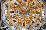 The domed ceiling of the Chapel of Our Lady of the Rosary shows the Virgin Mary and the infant Jesus enthroned on clouds with the Pious Nuns and Friars at her feet. They are surrounded by the Apostles. Santo Domingo de Guzmán, Oaxaca.