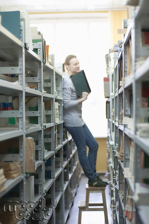 Woman stands on stool in library