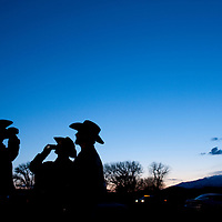 USA, Montana, Big Timber, Silhouette of cowboys drinking beers in parking lot after Bull-a-Rama rodeo on spring evening
