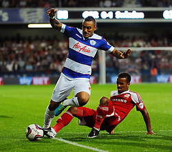 Queen Park Rangers' Danny Simpson is tackled by Swindon Town's Nathan Byrne  - Photo mandatory by-line: Seb Daly/JMP - Tel: Mobile: 07966 386802 27/08/2013 - SPORT - FOOTBALL - Loftus Road - London - Queens Park Rangers V Swindon Town -  Capital One Cup - Round 2