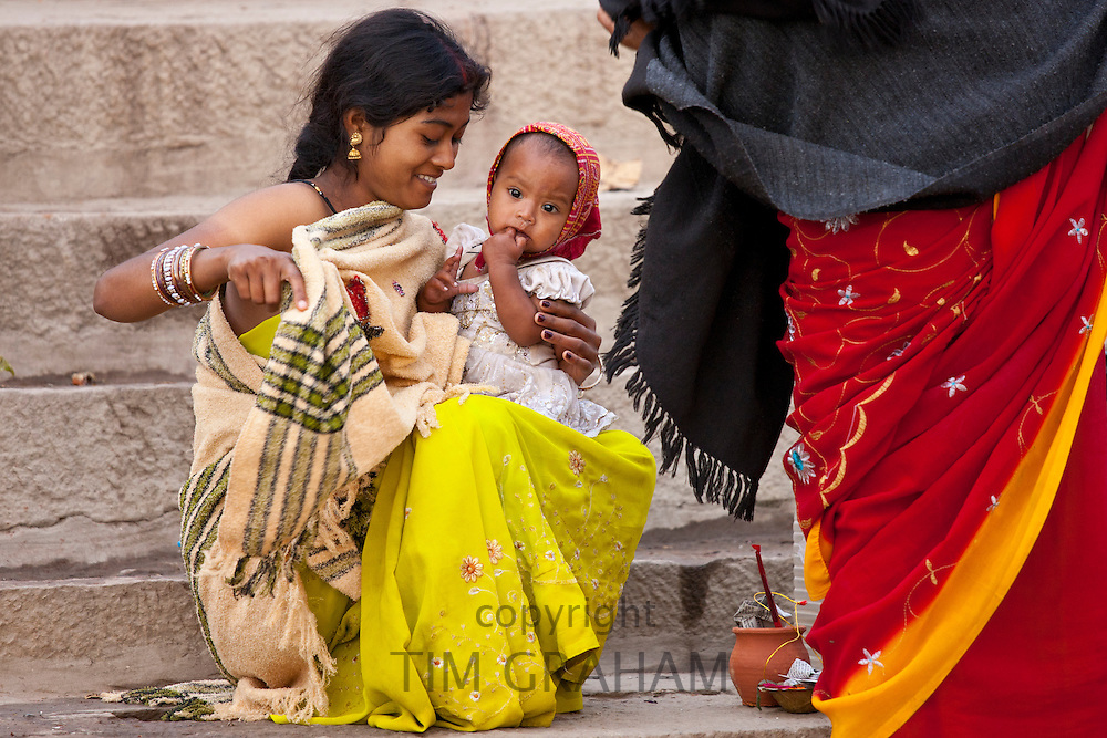 Indian Hindu mother comes to bathe her child in The Ganges River at Dashashwamedh Ghat in Holy City of Varanasi, India