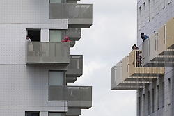 © Licensed to London News Pictures. 04/06/2017. LONDON, UK.  Residents watch from their balconies as four women are removed by police from the block of flats in Kings Road, Barking that police raided this today in connection with terror attack.  Photo credit: Vickie Flores/LNP