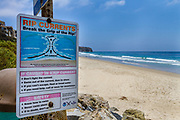 USA, California, Dana Point.  A sign warns of stromg rip currents in the Pacific Ocean off the coast of California.