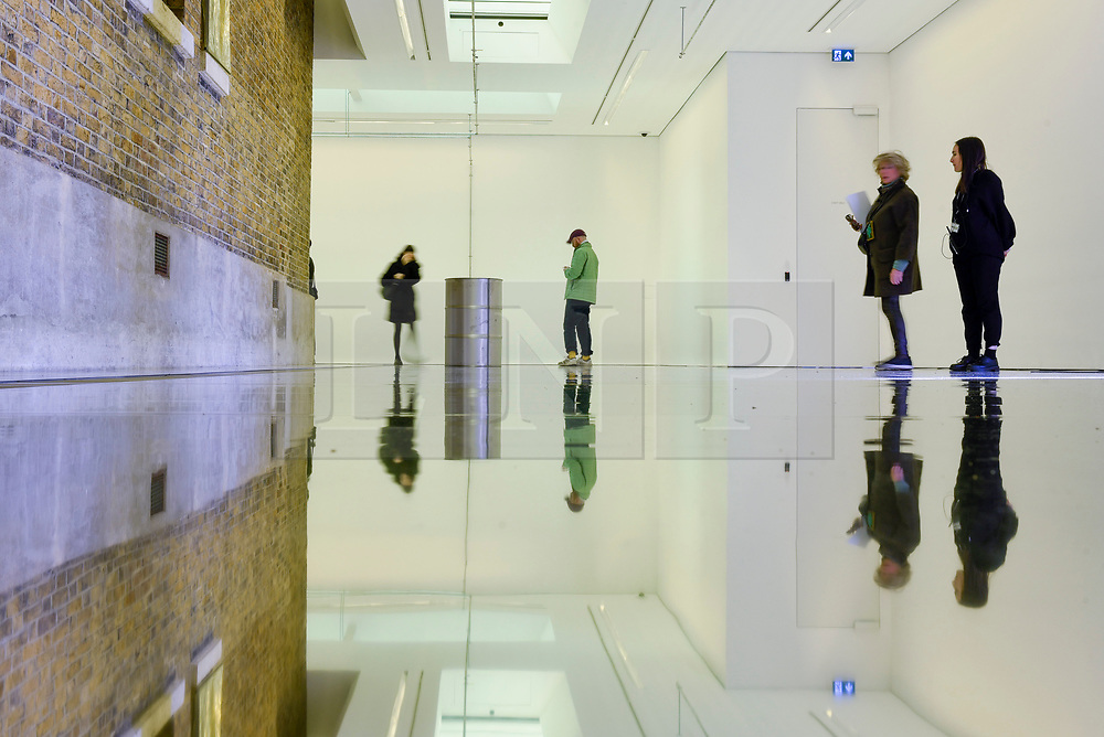 "© Licensed to London News Pictures. 07/11/2019. LONDON, UK.  General view of gallery space at the preview of ""On Venus"" by Patrick Staff, a site-specific exhibition commissioned by the Serpentine Sackler Gallery.  Altered lighting and reflective flooring combined with natural and synthetic liquids leaking from ceiling piping into steel barrels forms the major installation.   The exhibition, which also includes etchings and video work, runs 8 November to 9 February 2020.  Photo credit: Stephen Chung/LNP"
