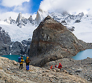"On the border between Argentina and Chile, Mount Fitz Roy rises into clouds 2500 meters (8200 feet) above Lago Sucia (left) in Los Glaciares National Park, in the southern Andes mountains, Patagonia, Argentina, South America. Hike to the glacial cirque of Laguna de los Tres (right) from El Chaltén village, which was built in 1985 by Argentina to help secure the disputed border with Chile. The frontier tourist town of El Chaltén is 220 km (3 hours drive) north of the larger town of El Calafate. In 1877, explorer Perito Moreno named ?Cerro Fitz Roy? for Robert FitzRoy (with no space before the capital R) who, as captain of the HMS Beagle, had travelled up the Santa Cruz River in 1834 and charted much of the Patagonian coast. First climbed in 1952 by French alpinists Lionel Terray and Guido Magnone, Mount Fitz Roy (3405 meters or 11,170 feet elevation) has fickle, windy weather and is one of the world's most challenging technical ascents. It is also called Cerro Chaltén, Cerro Fitz Roy, and Monte Fitz Roy (with a space before the R). Chaltén comes from a Tehuelche (Aonikenk) word meaning ""smoking mountain"" (explained by frequent orographic clouds). Cerro is a Spanish word meaning hill. The foot of South America is known as Patagonia, a name derived from coastal giants, Patagão or Patagoni, who were reported by Magellan's 1520s voyage circumnavigating the world and were actually Tehuelche native people who averaged 25 cm (or 10 inches) taller than the Spaniards. Mount Fitz Roy is the basis for the Patagonia company's clothing logo, after Yvon Chouinard's ascent and subsequent film in 1968. Panorama stitched from 2 overlapping photos."