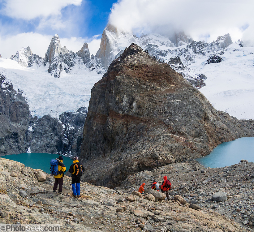 """On the border between Argentina and Chile, Mount Fitz Roy rises into clouds 2500 meters (8200 feet) above Lago Sucia (left) in Los Glaciares National Park, in the southern Andes mountains, Patagonia, Argentina, South America. Hike to the glacial cirque of Laguna de los Tres (right) from El Chaltén village, which was built in 1985 by Argentina to help secure the disputed border with Chile. The frontier tourist town of El Chaltén is 220 km (3 hours drive) north of the larger town of El Calafate. In 1877, explorer Perito Moreno named ?Cerro Fitz Roy? for Robert FitzRoy (with no space before the capital R) who, as captain of the HMS Beagle, had travelled up the Santa Cruz River in 1834 and charted much of the Patagonian coast. First climbed in 1952 by French alpinists Lionel Terray and Guido Magnone, Mount Fitz Roy (3405 meters or 11,170 feet elevation) has fickle, windy weather and is one of the world's most challenging technical ascents. It is also called Cerro Chaltén, Cerro Fitz Roy, and Monte Fitz Roy (with a space before the R). Chaltén comes from a Tehuelche (Aonikenk) word meaning """"smoking mountain"""" (explained by frequent orographic clouds). Cerro is a Spanish word meaning hill. The foot of South America is known as Patagonia, a name derived from coastal giants, Patagão or Patagoni, who were reported by Magellan's 1520s voyage circumnavigating the world and were actually Tehuelche native people who averaged 25 cm (or 10 inches) taller than the Spaniards. Mount Fitz Roy is the basis for the Patagonia company's clothing logo, after Yvon Chouinard's ascent and subsequent film in 1968. Panorama stitched from 2 overlapping photos."""