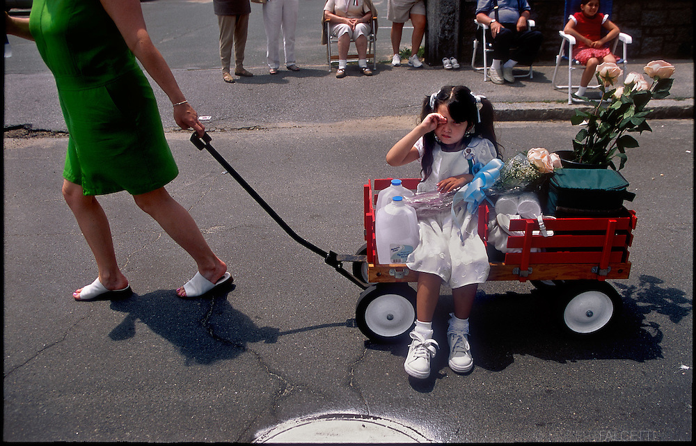 GLOUCESTER, MA- JUNE 29, 2003:  A small girl gets a ride on a wagon during the Sunday procession through the streets during the annual celebration paying homage to St. Peter, the patron saint of fishermen in Gloucester, MA. The festa takes place on the weekend closest to the Feast Day of St. Peter, June 29. .(Photo by Robert Falcetti) . .