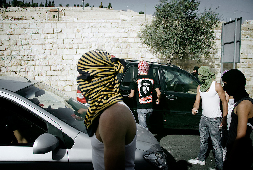Masked Palestinian stops car from passing through the East Jerusalem neighboorhood of Ras al-Amud March 12, 2010. Israeli forces sealed off the West Bank and massed riot squads around Jerusalem's Old City and Arab neighboorhoods during Muslim weekly prayers on Friday, facing down Palestinian anger over Jewish settlement expansion.