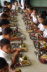 "Students eat lunch at the Florencio Jimenez school.  The school is one of the new ""Bolivarian"" Schools which are part of President Chavez's Education Reform.  The new Bolivarian Schools keep students for an entire day, as opposed to a half day, feed the students lunch and offer programs like drama, art and music. While President Chavez touts his programs that benefit the poor, many point to a rising poverty rate and shrinking economy and claim the programs fail to substantially help."