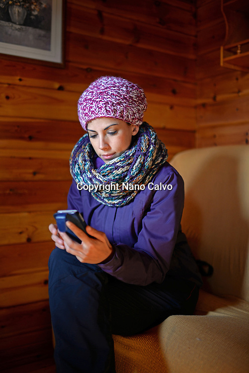Young woman using mobile phone in wood cottage