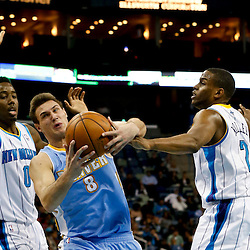 Mar 25, 2013; New Orleans, LA, USA; Denver Nuggets small forward Danilo Gallinari (8) is fouled as he drives between New Orleans Hornets small forward Al-Farouq Aminu (0) and small forward Darius Miller (2) during the second half of a game at the New Orleans Arena. The Hornets defeated the Nuggets 110-86. Mandatory Credit: Derick E. Hingle-USA TODAY Sports