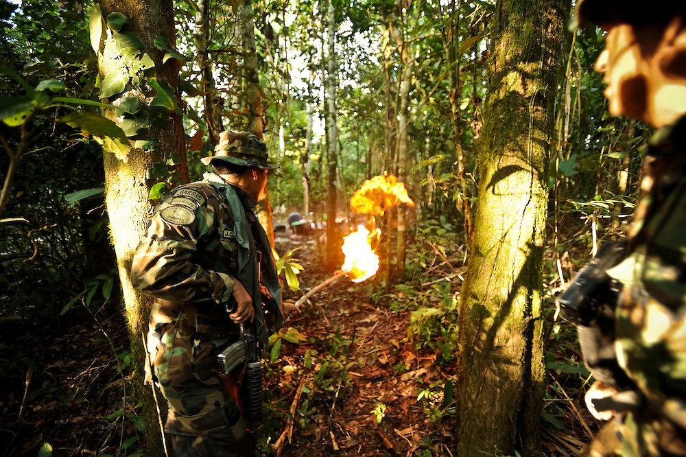 """Bolivian FELCN Special Forces agent, Juan Pablo Claros López, 25, lights a line of gasoline on fire during a raid to burn and destroy a cocaine-base processing lab in the outskirts of Villa Nuevo Horizonte, a dangerous area in the department of Santa Cruz were narcotraffiking runs rampant. FELCN officials report it is the area of Bolivia most thickly dense of narcotraffickers and cocaine-base processing laboratories.  FELCN police commonly referred to it as a """"narco pueblo""""."""