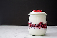 Parfait of yogurt and pomegranate seeds (arils) in a glass canning jar.