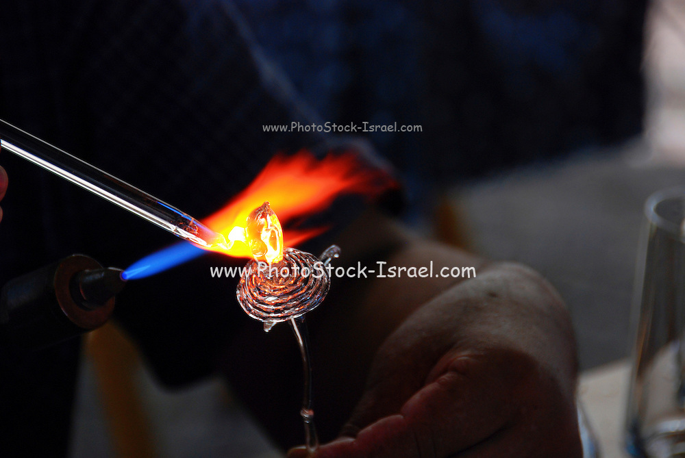 glass artist melting glass on a flame in his outdoor stall