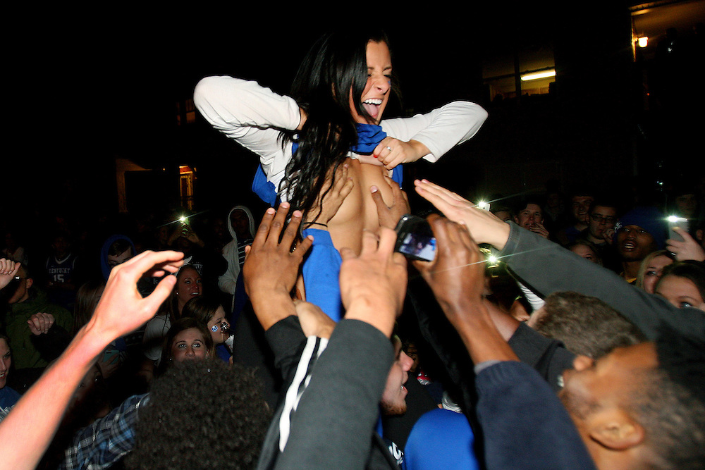 A female student, cheered on by a crowd of people, exposes herself on State Street following Kentucky's win over Wisconsin.