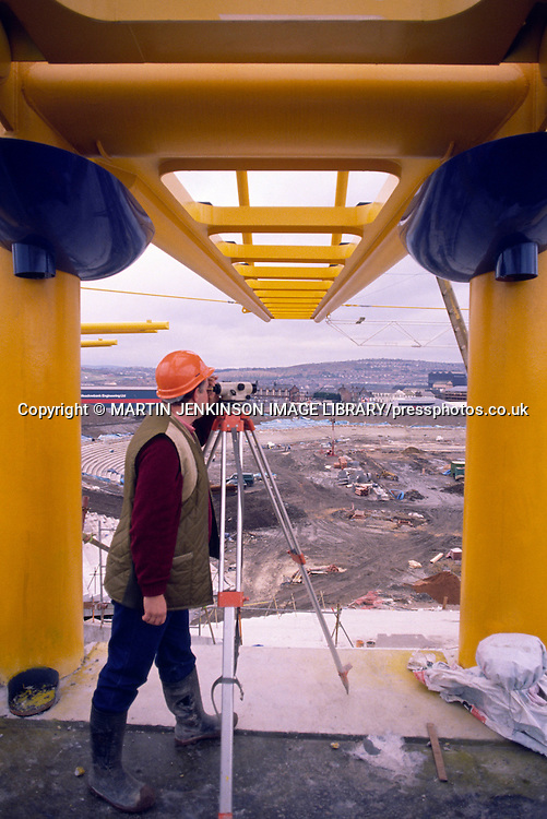 Surveyor using a theodolite during the construction of the Don Valley Stadium Sheffield ....