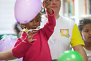 C&A volunteer decorating a balloon with children at their community library, Biblioteca Chocolatao, Porte Alegre, Brazil.