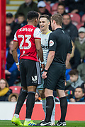 John Brooks (Referee) brings Julian Jeanvier (Brentford) and Tom Lawrence (Derby County) together to talk during the EFL Sky Bet Championship match between Brentford and Derby County at Griffin Park, London, England on 6 April 2019.