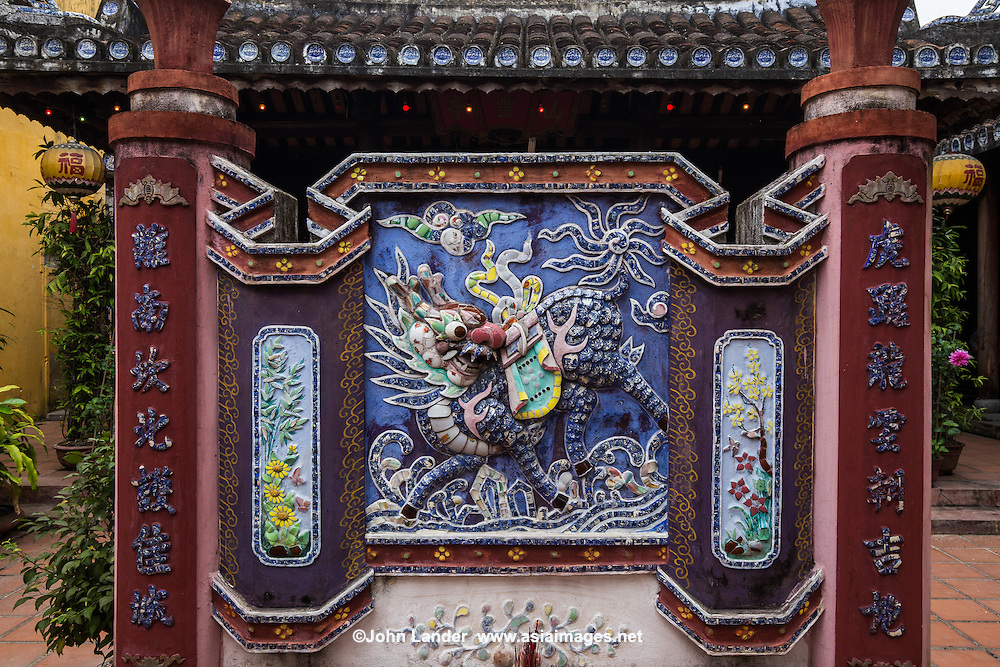 Decorative Bas Relief at Hainan Assembly Hall - Hainan Assembly Hall or Hoi Quan Hai Nam - was built by the overseas Chinese from Hainan Province who lived in Hoi An.  Their assembly hall is used to worship Chinese merchants who were falsely accused of being pirates, later they were named as deities by Vietnamese king Tu Duc who donated money and resources to have this assembly hall built for the sake of restoring their names and as a place for ancestor worship. One of the more intricate of architectural masterpieces in UNESCO Hoi An, visitors pass through a courtyard of ornamental trees, to the main hall dedicated to the Hainan Chinese killed at sea.  The God of Wealth is worshipped on the right.