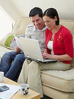 Couple using laptop sitting on sofa
