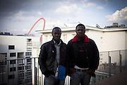 Migranti ritratti sul tetto di una delle palazzine dell'ex moi. Sullo sfondo la passerella olimpica.