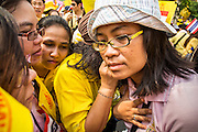 05 DECEMBER 2012 - BANGKOK, THAILAND: Women crowd around a radio to hear the King's address on the Royal Plaza Wednesday. Bhumibol Adulyadej, the King of Thailand, had a public audience and address at the Mukkhadej balcony of the Ananta Samakhom Throne Hall. December 5 is a national holiday. It's also celebrated as Father's Day. Celebrations are being held across the country to mark the birthday of Bhumibol Adulyadej, the King of Thailand.    PHOTO BY JACK KURTZ