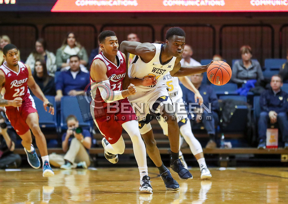 Nov 28, 2018; Morgantown, WV, USA; West Virginia Mountaineers forward Wesley Harris (21) dribbles the ball up the floor while defended by Rider Broncs guard Stevie Jordan (23) during the second half at WVU Coliseum. Mandatory Credit: Ben Queen-USA TODAY Sports