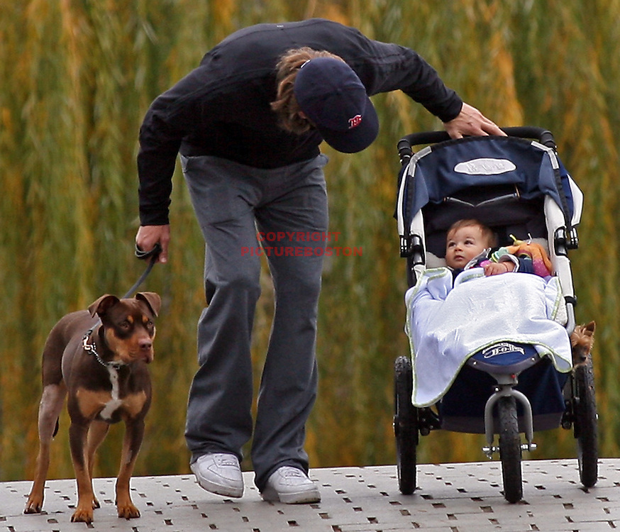 Tom Brady walks his dog Lua and his toddler Benjamin along the Charles River Tuesday afternoon, November 16,2010. Staff photo by Mark Garfinkel.