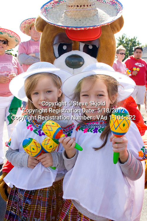 Happy young girls shaking maracas with bear mascot in the parade. Mexican Independence Day Minneapolis Minnesota MN USA