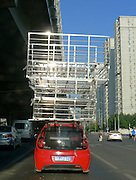 BEIJING, CHINA - AUGUST 25: (CHINA OUT) <br /> <br /> <br /> A car carrying several metallic frames is driven along a road on August 25, 2013 in Beijing, China. <br /> ©Exclusivepix