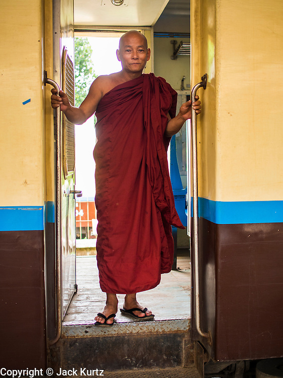 05 JUNE 2014 - YANGON, YANGON REGION, MYANMAR: A Buddhist monk stands in the doorway of a rail car on the Yangon Circular Train. The Yangon Circular Train is a commuter train that circles Yangon, Myanmar (Rangoon, Burma). The train is 45 kilometers long, makes 38 stops and takes about three hours to make a loop of the city.     PHOTO BY JACK KURTZ