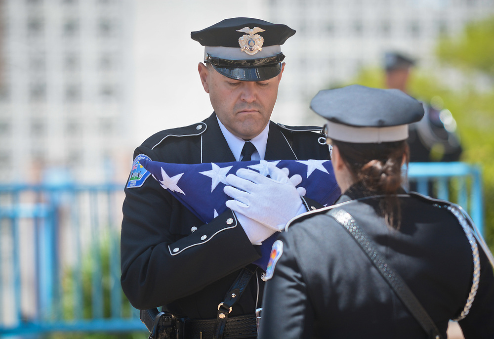 mkb050217b/metro/Marla Brose -- Albuquerque Police Ofc. Daren DeAguero holds the American flag after the folding ceremony in honor of New Mexico law enforcement officers killed in the line-of-duty during the annual Law Enforcement Memorial Service at Civic Plaza in Albuquerque, N.M., May 2, 2017. (Marla Brose/Albuquerque Journal)
