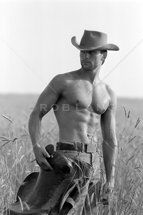 shirtless All American cowboy holding a saddle in an open field