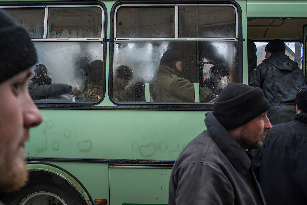 SARTANA, UKRAINE - FEBRUARY 5, 2015: After stopping at a local supermarket to stock up on snacks, Ukrainian soldiers board their bus on the way to front-line areas in Sartana, Ukraine. With more than 220 people having died in the past several weeks, a new diplomatic push is underway to bring an end to fighting between pro-Russia rebels and Ukrainian forces. CREDIT: Brendan Hoffman for The New York Times