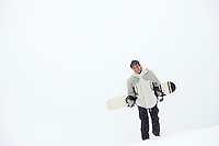 Man walking on snow carrying snowboard