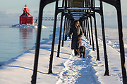 A middle aged woman walk her dog  at a lighthouse on Lake Michigan in Sturgeon Bay, Wisconsin on a cold winter day.