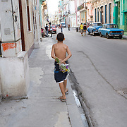 Young boy in Havana, Cuba taking flowers to his mother.<br />