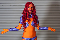 © Licensed to London News Pictures. 14/03/2015. Newham, London, UK.  A gir dressed as Starfire from DC Comics, one of many cosplayers attending the London Comic Con at the Excel Centre in Docklands. Photo credit : Stephen Chung/LNP