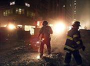 WTC--Fighting choking and blinding dust and debris firemen move along near the crash scene.