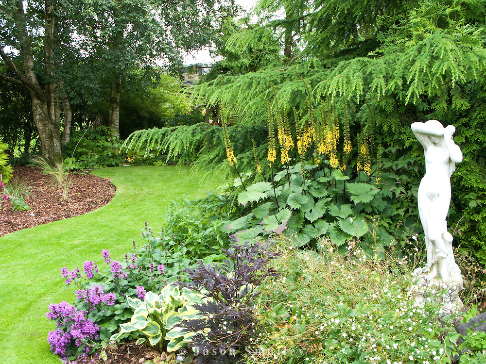 statue of a lady in a deep flower bed.