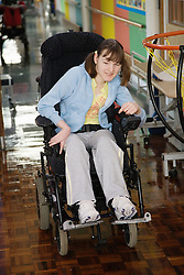 Young girl with physical disability entering school sports hall,