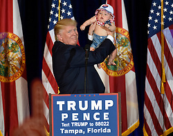 November 5, 2016 - Tampa, Florida, U.S. - Republican candidate for President DONALD TRUMP holds up 6 month-old CATALINA LARKIN, of Largo, up on stage while Trump spoke to supporters during a rally Saturday three days before elections. (Credit Image: © Chris Urso/Tampa Bay Times via ZUMA Wire)