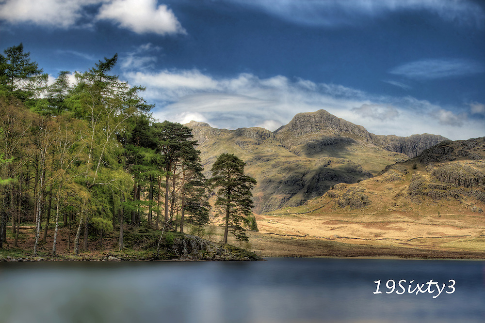 Dramatically beautiful Blea Tarn, one of the Lake District's innumerable small tarns, occupies a ridge between the Little Langdale Valley and Dungeon Ghyll in Great Langdale. The name blea derives from dark blue.<br /> Set in a superbly panoramic location beneath the shadows of the rugged Langdale Pikes, the tarn stands 700' above sea level. The shores of Blea Tarn are awash with a carpet of wild alpine flowers in the spring and summer.