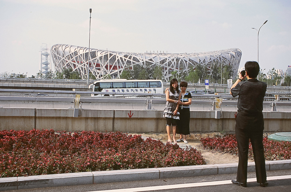 Olympics are coming<br /> A picture with the Olympic stadium...<br /> Some chinese tourists are taking pictures of themselves with the olympic stadium (also called the Bird Nest) in the background. Every day near the third ring, hundreds of beijingers and tourists try to see the olympic stadium and the swimming pool which are still closed to the public. Beijing, China, july 20 2008<br /> High resolution available.