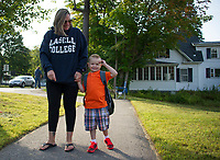 Mitchell Day is all smiles on Thursday morning with his mom Sarah Lamontagne. Day will begin his first day of Kindergarten on his 5th birthday.    (Karen Bobotas/for the Laconia Daily Sun)