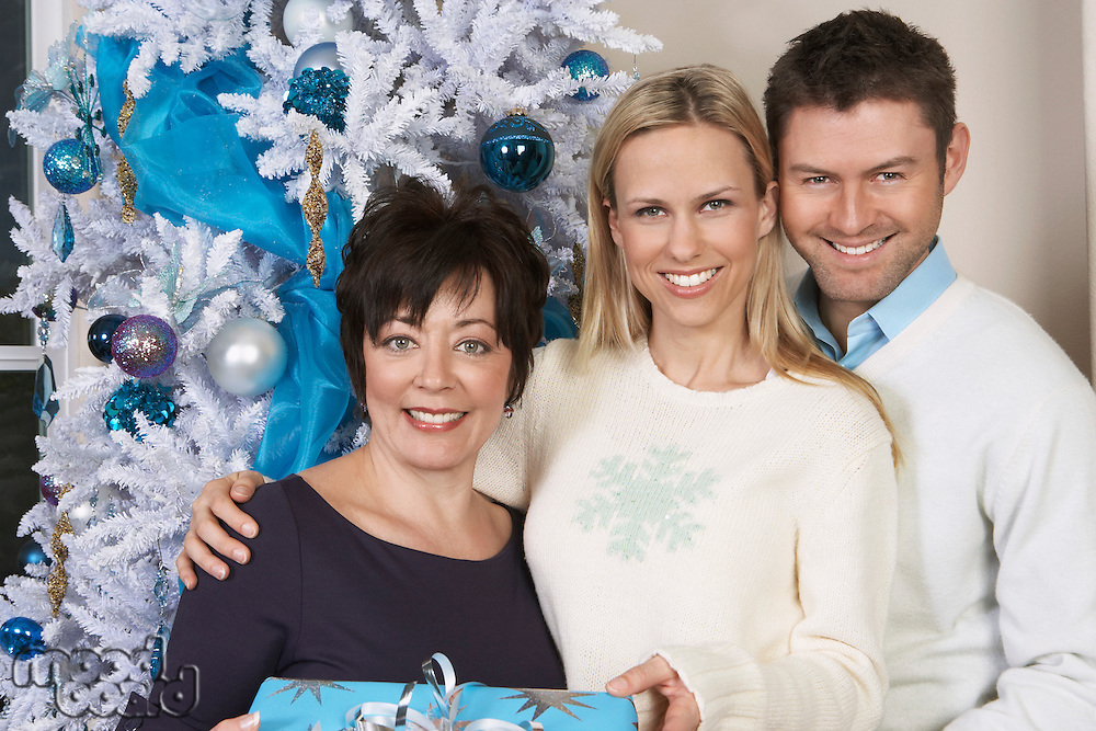 Senior woman and mid adult couple in front of Christmas tree, portrait