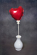 a red, heart-shaped balloon in a white vase